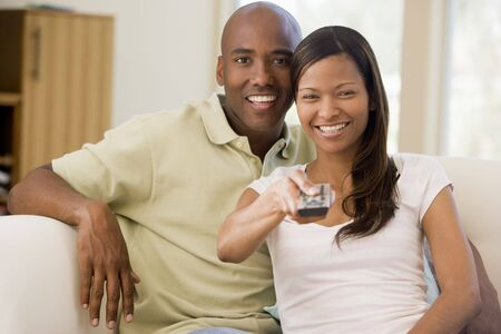woman watching tv: Couple in living room with remote control smiling Stock Photo