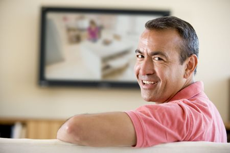television camera: Man in living room watching television smiling