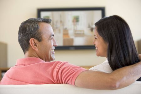 early 40s: Couple in living room watching television smiling