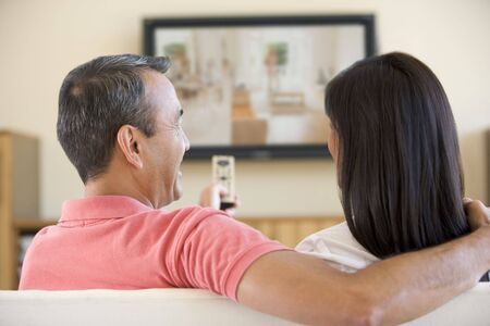 early 40s: Couple in living room watching television laughing