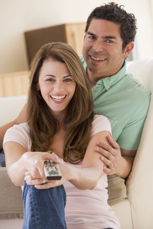 latin looking: Couple in living room with remote control smiling Stock Photo
