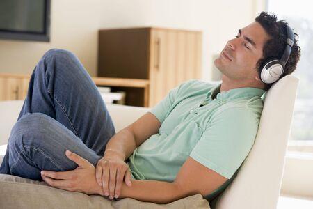 listening to music: Hombre en la sala escuchando auriculares para dormir