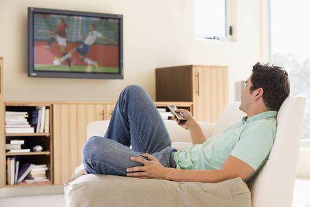 personas mirando: Hombre en la sala viendo la televisión