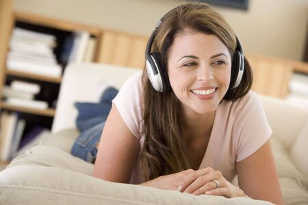 Woman in living room listening to headphones smiling Stock Photo - 3482909