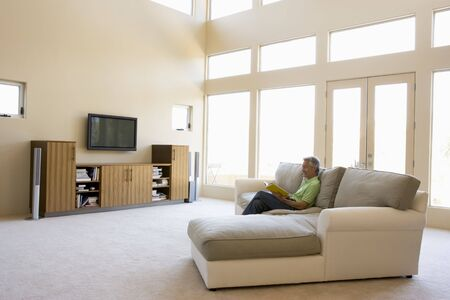 Man reading book in living room smiling Stock Photo - 3484694