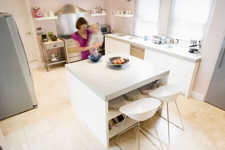 whisking: Woman in kitchen whisking on counter holding