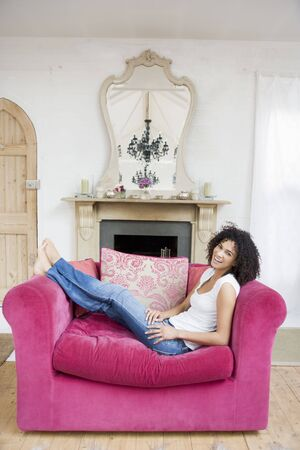 early thirties: Woman sitting in living room smiling