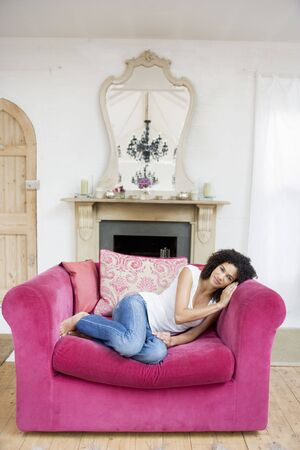 generation x: Woman sitting in living room smiling