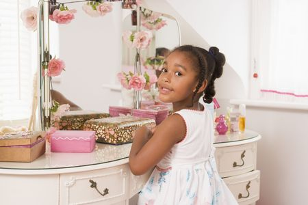 Young girl sitting at mirror in bedroom smiling photo