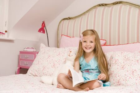 Young girl sitting on bed with book smiling photo