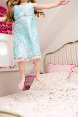 Young girl jumping on bed Stock Photo - 3485111