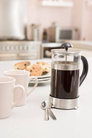 Coffee pot on kitchen counter with scones photo
