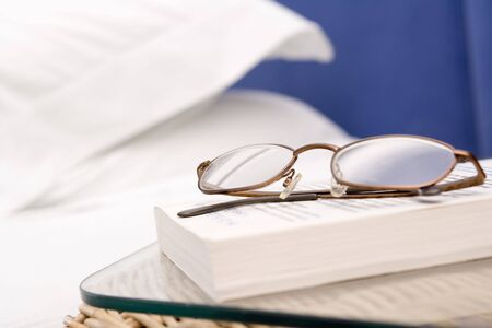 bedside: Empty bedroom with focus on eyeglasses and book Stock Photo