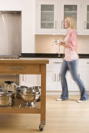 Woman walking in kitchen holding coffee photo