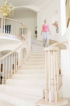 Woman coming down staircase in luxurious home photo