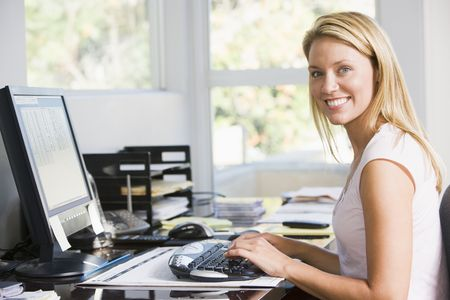 home office desk: Woman in home office with computer smiling Stock Photo