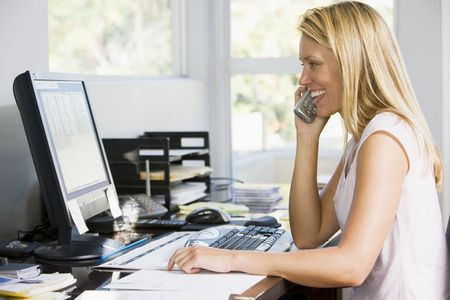 trabajando en casa: Mujer en oficina en casa con ordenador utilizando tel�fono sonriente