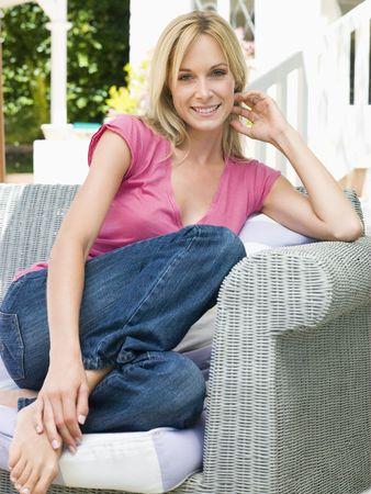 mid twenties: Woman sitting outdoors on patio smiling