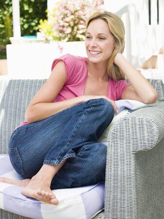 mujeres sentadas: Mujer sentada en el patio al aire libre sonriente