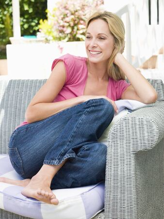 Woman sitting outdoors on patio smiling photo