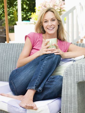 Woman sitting outdoors on patio with coffee smiling photo
