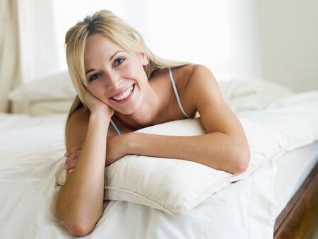 Woman lying in bedroom smiling photo