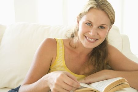 Woman in living room reading book smiling Stock Photo - 3483091