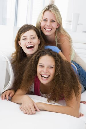 Three women in living room playing and smiling photo
