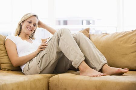 Woman in living room listening to MP3 player smiling Stock Photo - 3484555