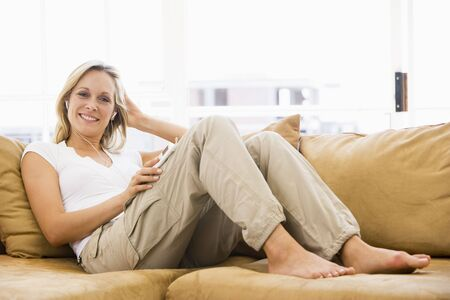 Woman in living room listening to MP3 player smiling photo