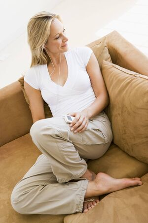 Woman in living room listening to MP3 player smiling Stock Photo - 3485601