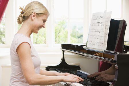 piano de cola: Mujer tocando el piano y sonriente