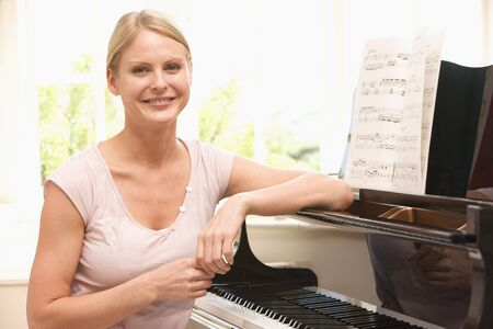Woman sitting at piano and smiling photo