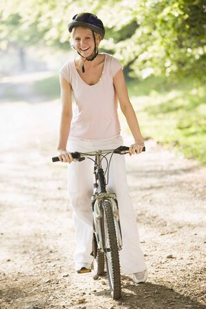 healthy path: Woman on bicycle smiling