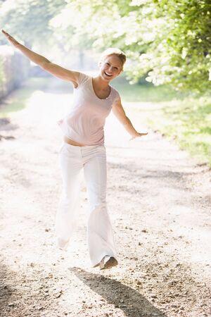 generation x: Woman walking on path smiling