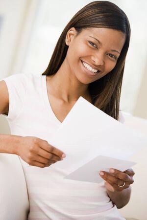 mujeres sentadas: Mujer en sala de lectura de los documentos de la sonrisa Foto de archivo