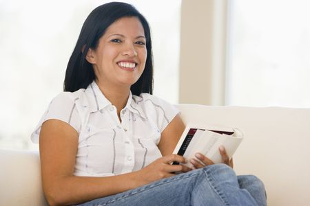 Woman in living room reading book smiling Stock Photo - 3482936