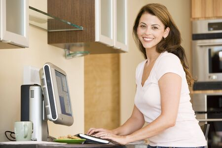 Woman in kitchen with computer smiling Stock Photo - 3485371