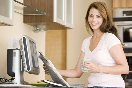 Woman in kitchen at computer with newspaper and coffee smiling Stock Photo - 3485264