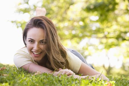 Woman lying outdoors smiling photo
