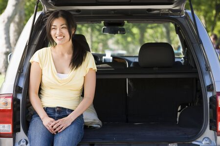 mpv: Woman sitting in back of van smiling Stock Photo