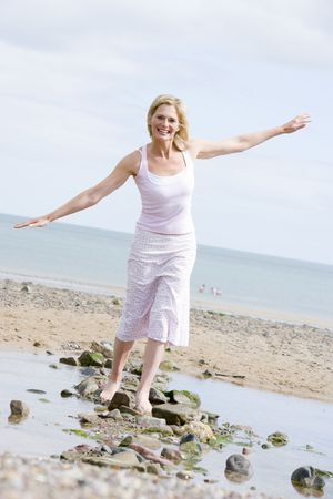 Woman walking on beach path smiling photo