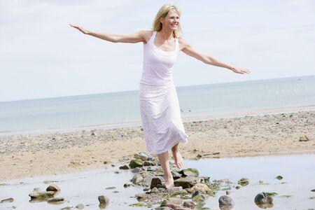 balancing: Woman walking on beach path smiling
