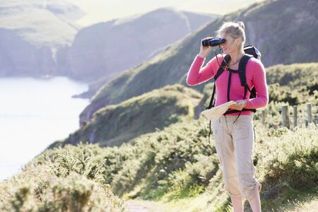 ruck sack: Woman on cliffside path using binoculars
