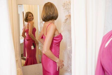 changing clothes: Mujer tratando en vestidos y sonriendo  Foto de archivo