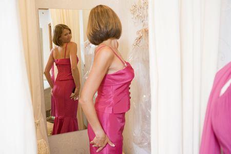changing clothes: La mujer intenta en vestidos y frowning  Foto de archivo