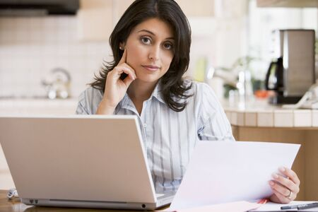 Woman in kitchen with laptop photo