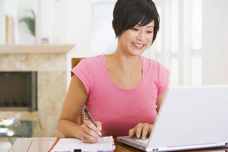 mujeres sentadas: Mujer en el comedor con ordenador port�til sonriente