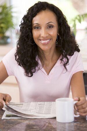 mujeres sentadas: Mujer en la cocina con el peri�dico y el caf� sonriendo Foto de archivo