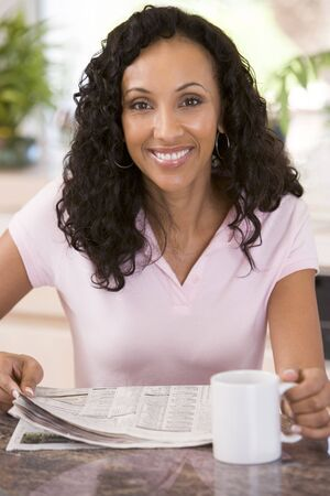 mature adult women: Woman in kitchen with newspaper and coffee smiling
